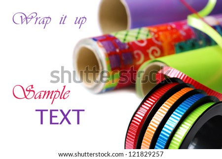 Brightly colored curling ribbon on spool with rolls of wrapping paper on white background with copy space.  Macro with shallow dof.