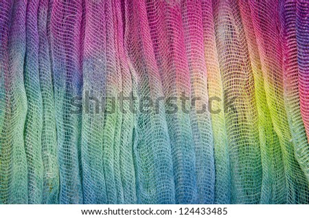 Brightly colored dyed fabric with a loose weave.