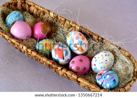 Brightly colored Easter eggs in a oval wicker basket nest with natural straw. Bright happy colors. Top view. #1350667214