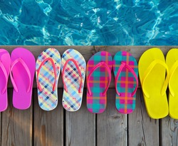 Brightly colored flip-flops on wooden background near the pool