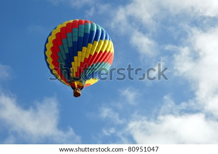 Brightly colored hot air balloon against cloudy blue sky