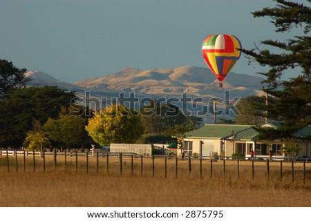 Brightly colored Hot air balloon over farmland