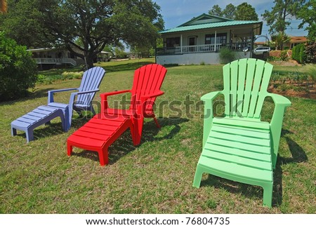 Brightly colored lawn furniture with small summer cottage in background.