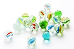 Brightly colored marbles in different shades on bright white