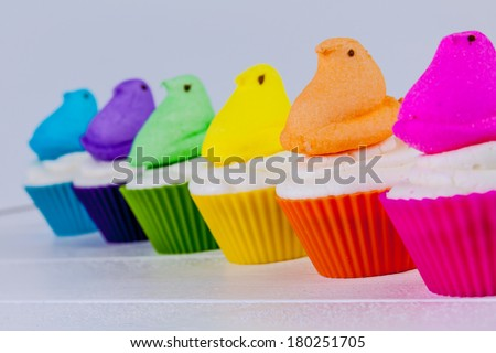 Brightly colored Peeps marshmallow Easter cupcakes arranged in rainbow