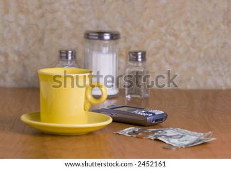 Brightly colored yellow cup of coffee and cellphone on a table at the diner.  Dollar bills and change on the table.  Sall, pepper, and a sugar jar are in the background.  Main focus on the cellphone.