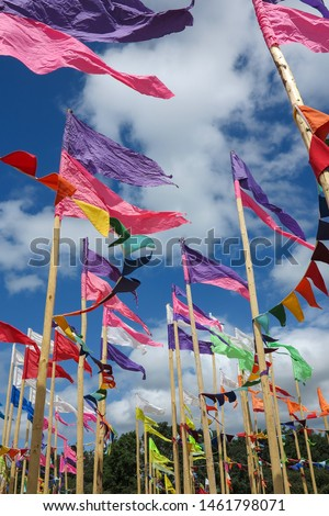 Brightly coloured flags wave against a bright blue sky with clouds.  Image has copy space. #1461798071