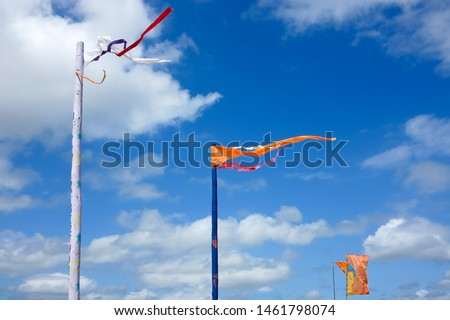 Brightly coloured flags wave against a bright blue sky with clouds.  Image has copy space. #1461798074