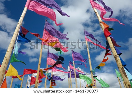 Brightly coloured flags wave against a bright blue sky with clouds.  Image has copy space.