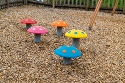 Brightly coloured mushroom shaped stepping stones on a children's playground outside in summer   Red, Pink, blue, orange, yellow