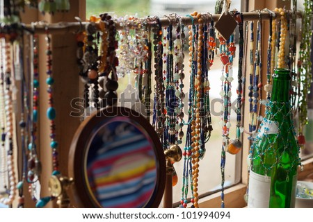 Brightly coloured necklaces, hanging in the window of a bric-a-brac shop.