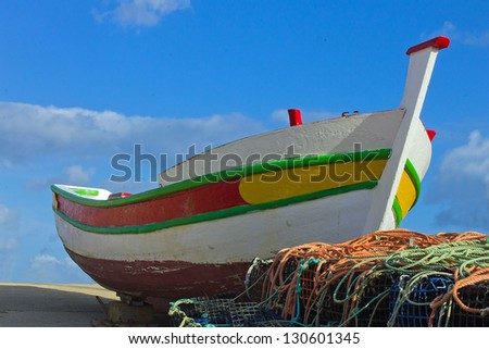 Brightly coloured Portuguese fishing boat pulled up on the hard with a tangle of fishing nets