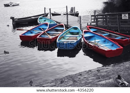 Brightly coloured rowing boats on a Scottish loch.