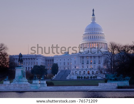 Brightly lit dawn sky behind the illuminated dome of the Capitol in Washington DC with the pool and statues - stock photo