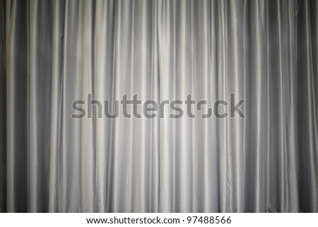 Brightly lit gray curtain for your background, like a theater stage
