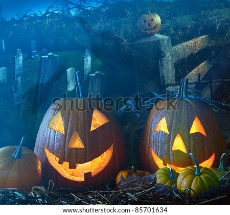 Brightly lit Halloween pumpkins in a grave yard