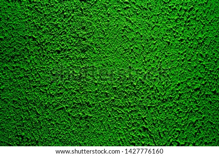 Brightly lit surface covered with bright green plaster. Trend color