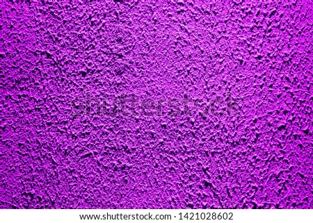 Brightly lit surface covered with bright purple plaster. Trend color