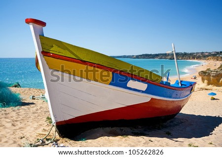 Brightly painted Iberian fishing boat on a sandy beach with a blue sea coastal background