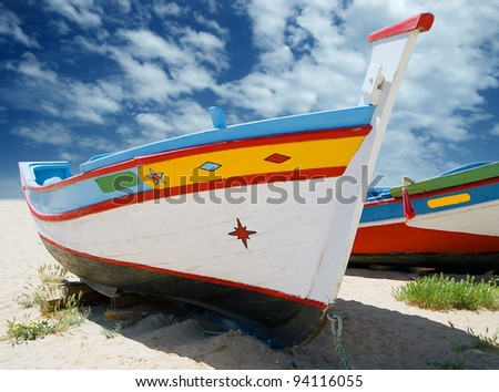 Brightly painted iberian fishing boats on the beach