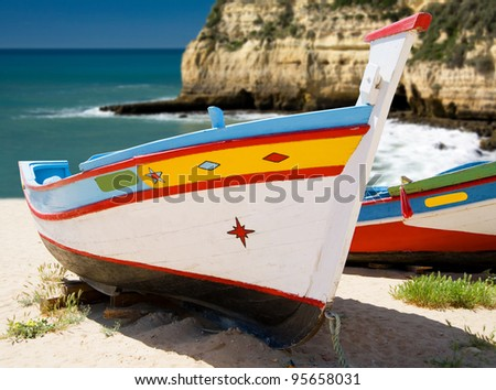 Brightly painted iberian fishing boats on the beach - stock photo
