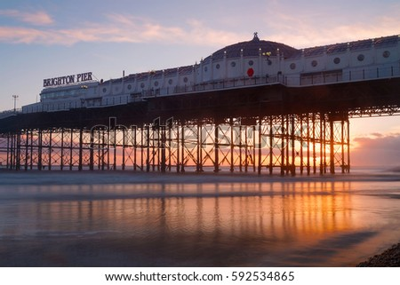 Brighton pier at sunset, warm red and orange colors. The pier reflecting in the water #592534865