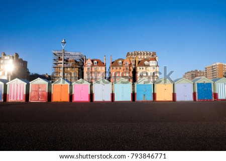 Brighton seafront 13 multi coloured beach huts, on Brighton beach promenade behind is blue sky and 3 victorian buildings, one of the buildings has scaffolding all over it, infront is the promenade