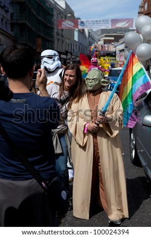 BRIGHTON, UK - AUG 13. LGBT participant in the Yoda costume from Star Wars movie taking photo with a tourist, in the pride parade at Brighton Pride Festival on August 13, 2011. - stock photo