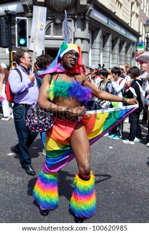 BRIGHTON, UK - AUG 13. The colorful dancer, one of the participants from the LGBT community dance with rainbow flag in the pride parade at Brighton & Hove Pride Festival on August 13, 2011. - stock photo