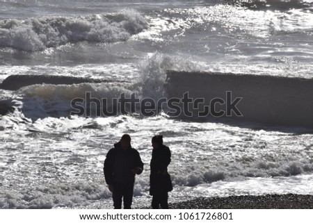 Brighton, United Kingdom - March 27 2018:   a couple watching the rough sea on the beach silhouetted by the sun reflecting off the water #1061726801