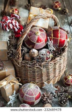 Brights Christmas Toys with gifts. Basket, Red balls, Pine cones, Boxes, Walnuts, Snowflakes, Sweet Candies on Wooden Table. Vintage style