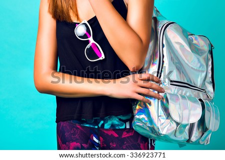 Brigit fashion details, stylish sportive woman wearing crazy mirrored silver backpack, printed pants and clear vintage sunglasses, mint background.