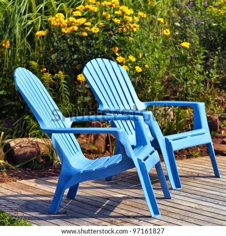 brilliant blue plastic outdoor adirondack chairs on the deck in a