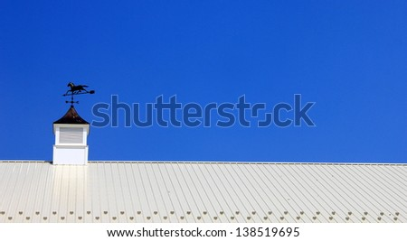 Brilliant blue summer sky and the vivid color of white metal roofing with weathervane cupola on top