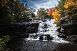 Brilliant fall foliage surrounds the beautiful cascading Shohola Falls in the Pennsylvania Poconos