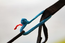 brilliant knot soft shackle woven of blue nylon or polyester rope on nature background. lighter than a carabiner. Tourist equipment