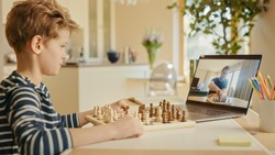 Brilliant Little Boy Playing Chess with His Chess Master, Uses Laptop for Video Call. Remote Online Education, E-Education, Distance Learning, Homeschooling.
