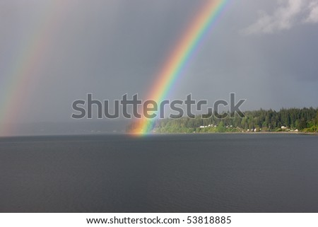 Brilliant rainbow over water and land. Bainbridge Island is seen accross Port Orchard Bay. Located in Kitsap County, Washington.