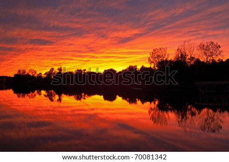 Brilliant red sunset and shoreline of Lake Doster with reflections in calm water, Michigan, USA
