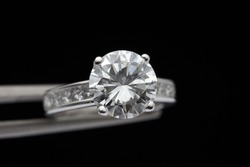 Brilliant round diamond ring is being held by a tweezers on black background