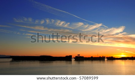 Brilliant sunset over moored WWII freighters.