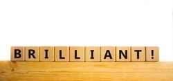 Brilliant symbol. The word brilliant on wooden cubes. Beautiful wooden table, white background. Business and brilliant concept. Copy space.
