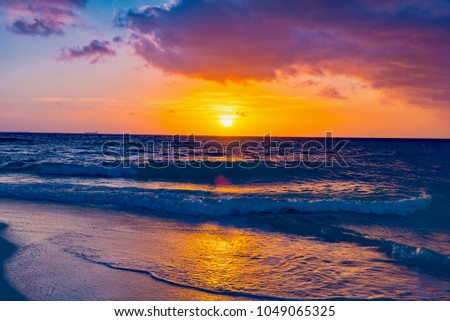 Brilliant vacation destination beach sunrise with colorful sand bright sea foam pink clouds  #1049065325