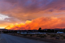 Brilliantly colored sunset in the desert over a community during a wildfire with smoke in the air road on left side