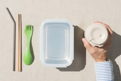 Bring your own container and cup awareness campaign for Zero waste. Hand or a man preparing his daily durable personal washable container, Stainless straw, chopstick, lunch box, coffee cup with lid.
