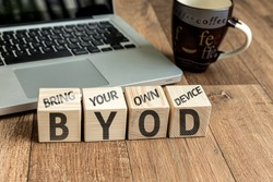 Bring Your Own Device (BYOD) written on a wooden cube in front of a laptop