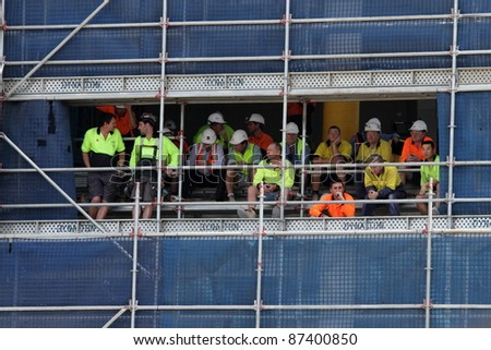 BRISBANE, AUSTRALIA  OCT 24 : Unidentified construction workers stop work to view the Queen Elizabeth 11 visit on October 24, 2011 in Brisbane, Australia