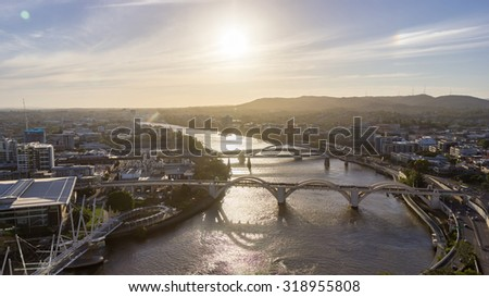 Brisbane City, Beautiful Panorama Aerial View of Kurilpa Bridge, William Jolly Bridge and Merivale Bridge over Brisbane River with Cityscape and Light Trails at Sunset in Summer, Queensland, Australia #318955808