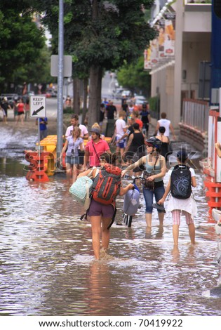 BRISBANE, QUEENSLAND/AUSTRALI A - JANUARY 13: People walking through flooded streets on January 13, 2011 in South Bank, Brisbane, Queensland, Australia. - stock photo