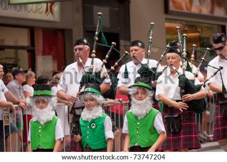 BRISBANE, QUEENSLAND/AUSTRALIA - MARCH 12: Back pipe band and three disguised boys on the annual St. Patrick's day parade on March 12, 2011 in Elizabeth Street, Brisbane.